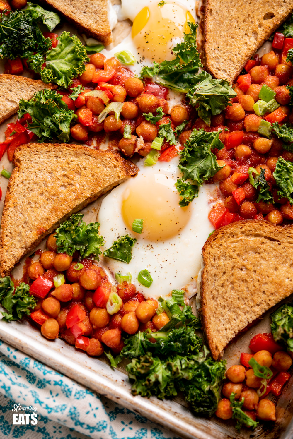 chickpeas, egg and kale on tray with crispy toast