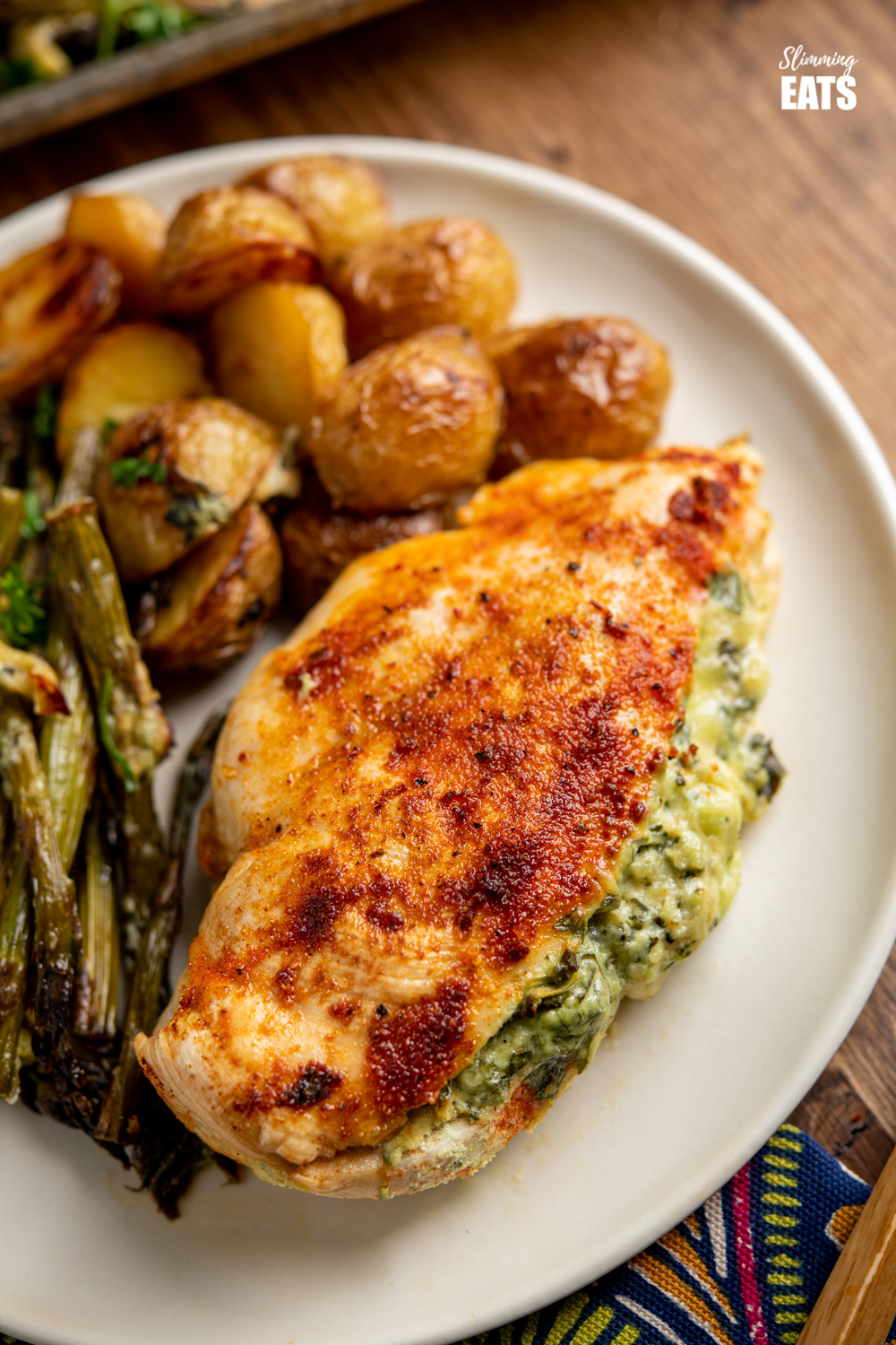 close up of Creamy Cheesy Spinach Stuffed Chicken on plate with asparagus and roasted baby potatoes