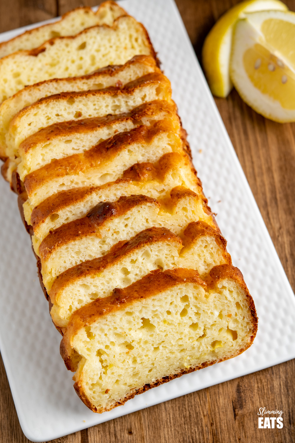 close up of sliced lemon loaf on white plate