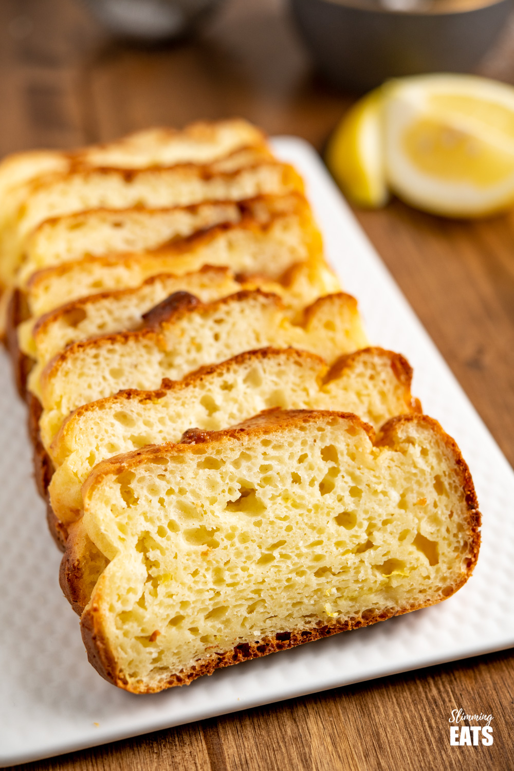 close up of lemon ricotta loaf on white place with lemon slices in background