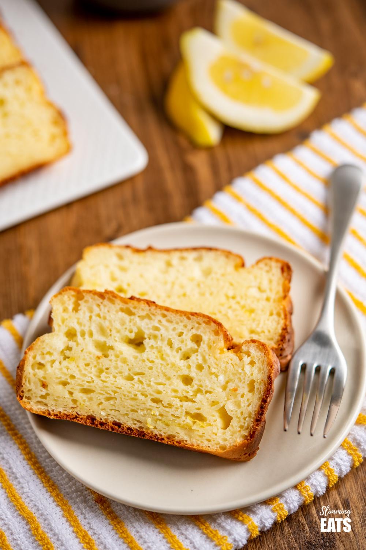 2 slices of lemon ricotta cake on cream plate with fork