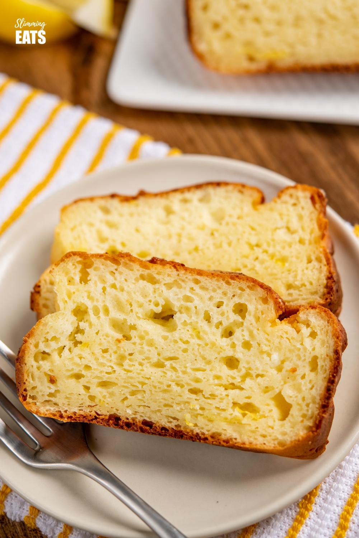 close up of 2 slices of lemon ricotta cake on cream plate