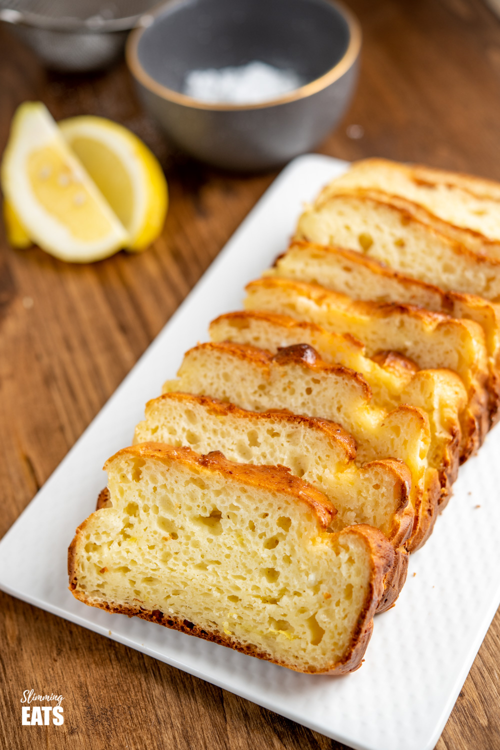 sliced lemon ricotta loaf on white plate with lemon slices in background