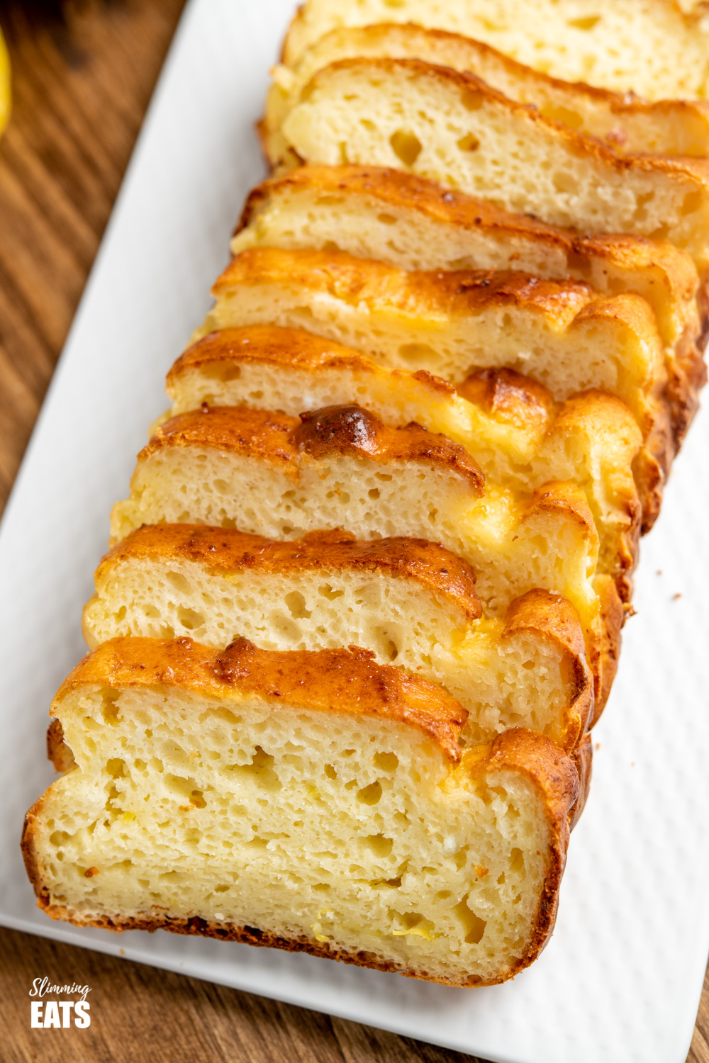 close up of sliced lemon ricotta loaf on white plate