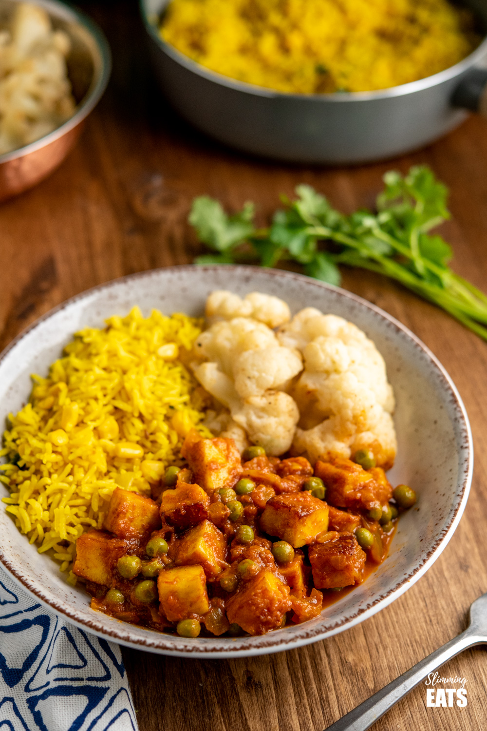 matar paneer curry in black frying pan in speckled bowl with roasted cauliflower and rice