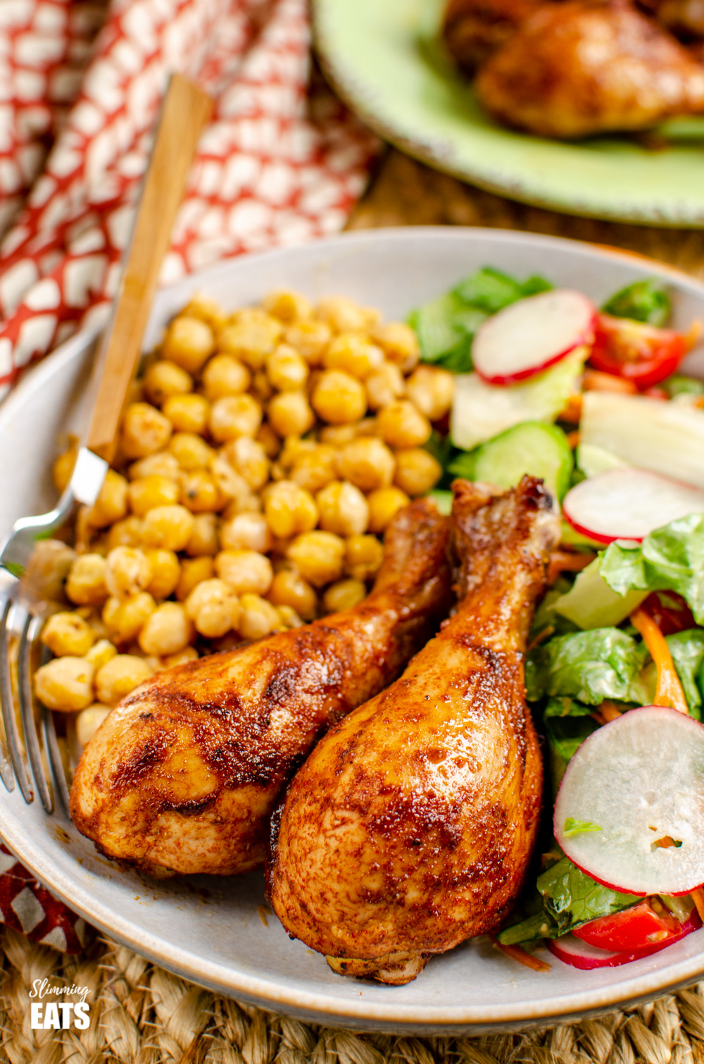 Paprika Balsamic Chicken Drumsticks in bowl with chickpeas and a mixed salad