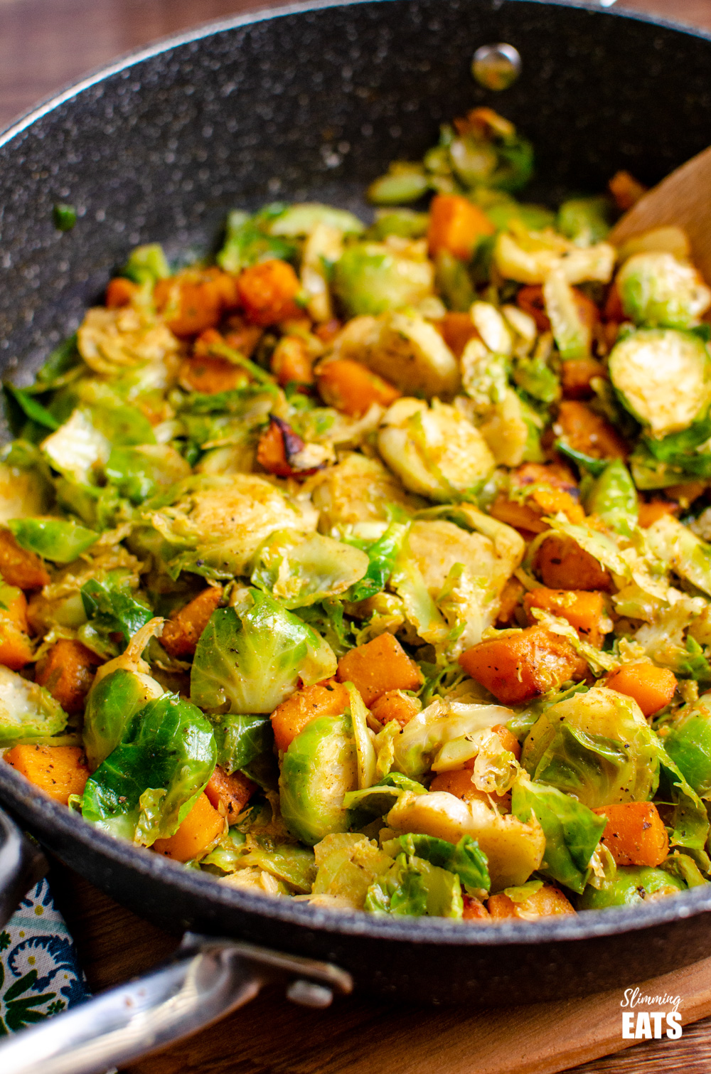 Sautéed Brussel Sprouts with Roasted Butternut Squash in black frying pan
