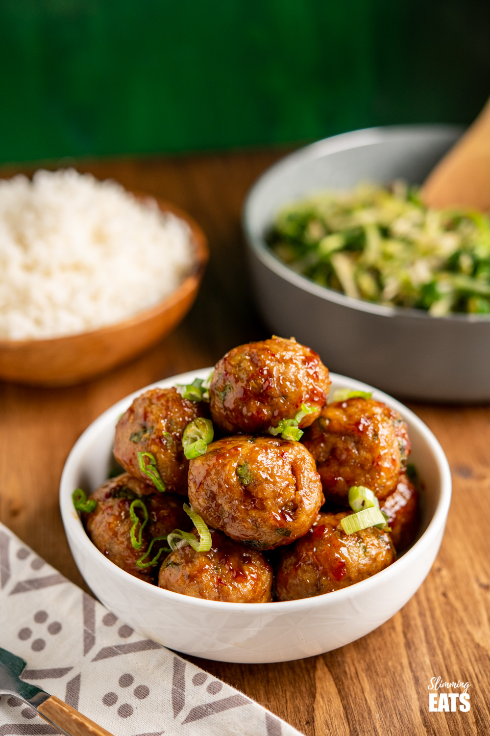 sweet chilli chicken meatballs in white bowl sprinkled with spring onion