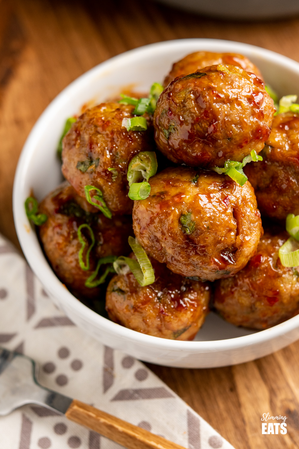 close up of sweet chilli meatballs in white bowl sprinkled with chopped spring onion.