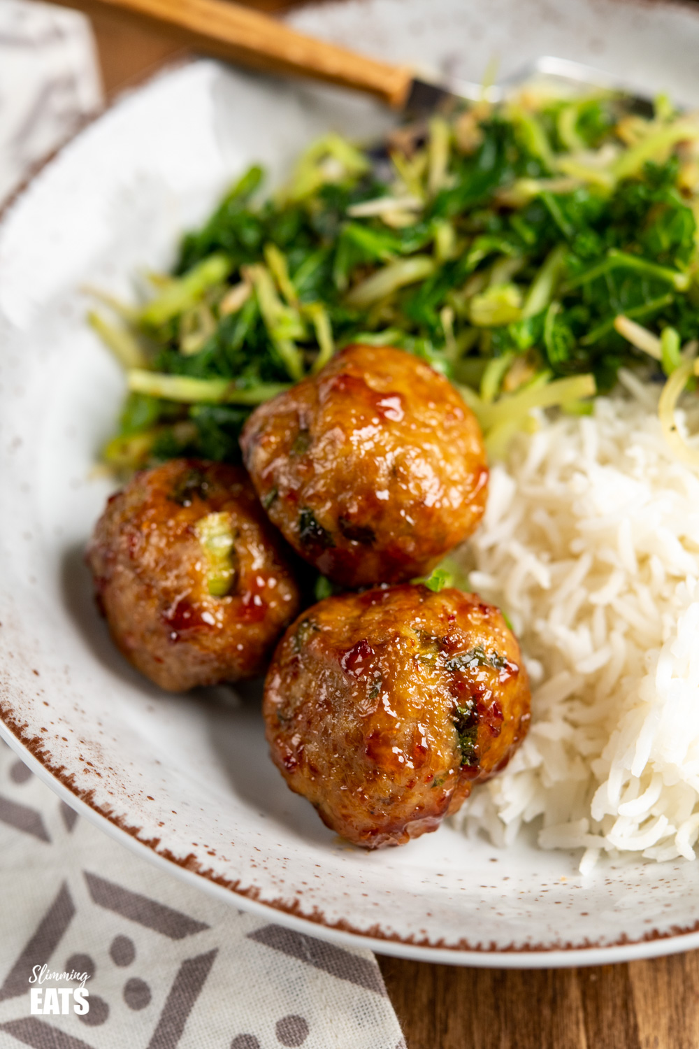 close up of sweet chilli chicken meatballs in bowl with rice and veggies