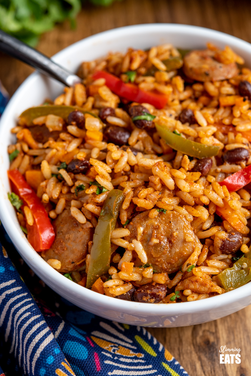 close up One Pot Cuban Style Rice in white bowl with black handled fork