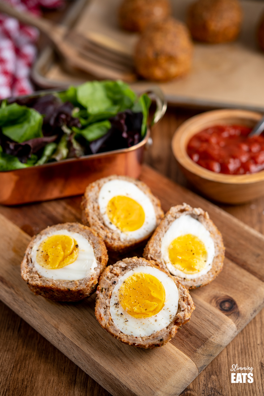 Oven Baked Scotch Eggs sliced in half on a wooden board with salad and relish