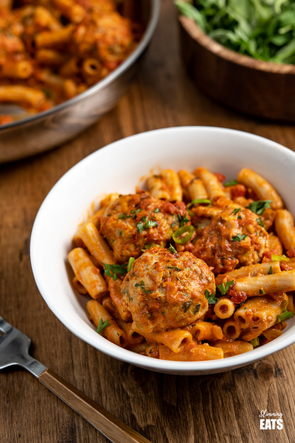white bowl with creamy cajun meatball pasta and wooden bamboo bowl of arugula in background
