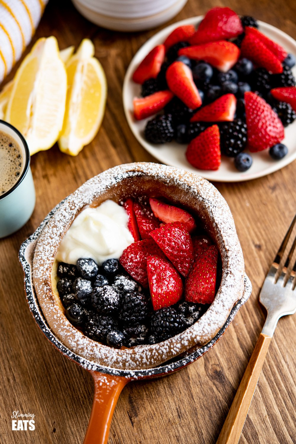 Dutch Baby in mini cast iron skillet with Berries and Yoghurt on a Wooden board with white bowl of berries and lemon wedge