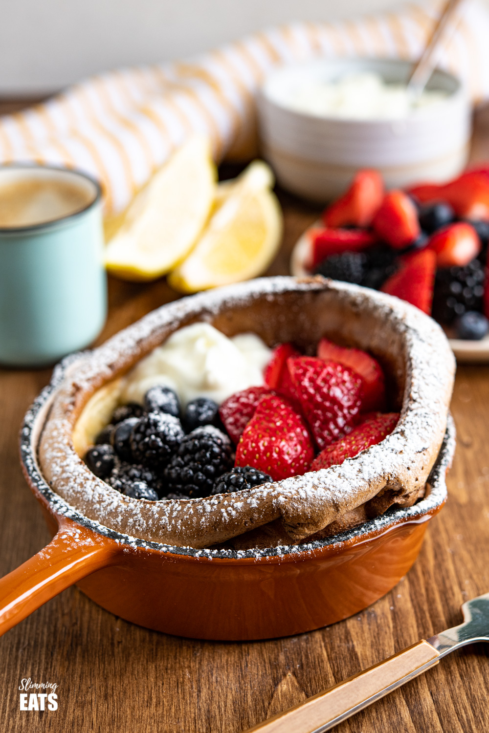 Healthier Dutch Baby with Berries and Yoghurt in cast iron skillet