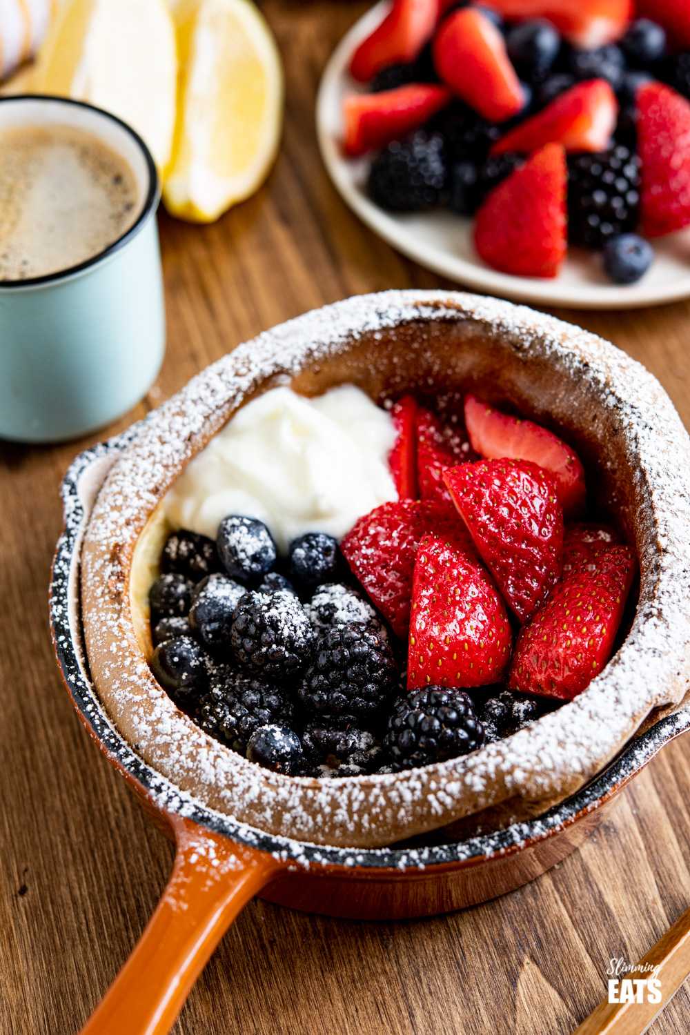 Healthier Dutch Baby with Berries and Yoghurt dusted with icing sugar in cast iron skillet