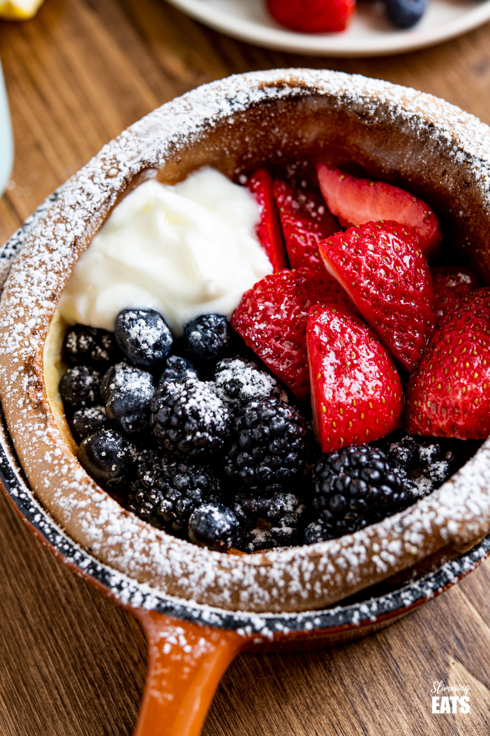 close up of Healthier Dutch Baby with Berries and Yoghurt in cast iron skillet dusted with icing sugar