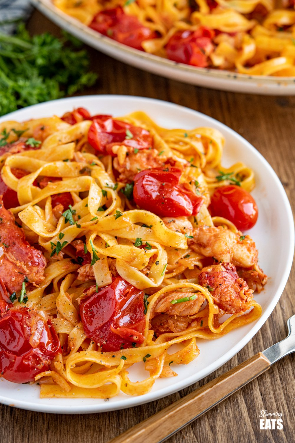 close up of serving of lobster pasta on white plate
