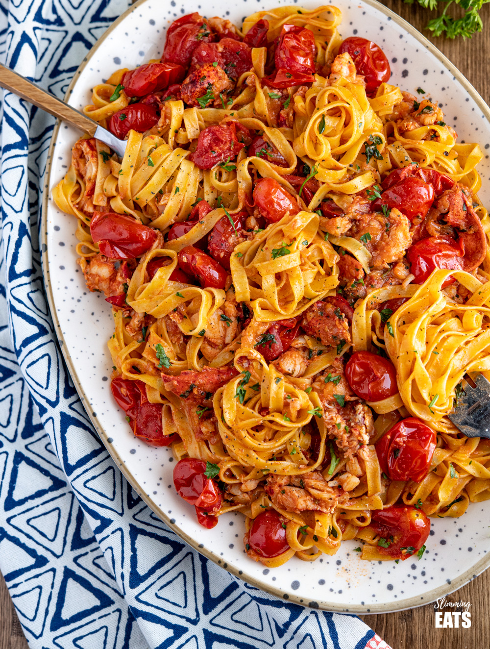Lobster Pasta on a large oval speckled dish with two forks spiralling the tagliatelle