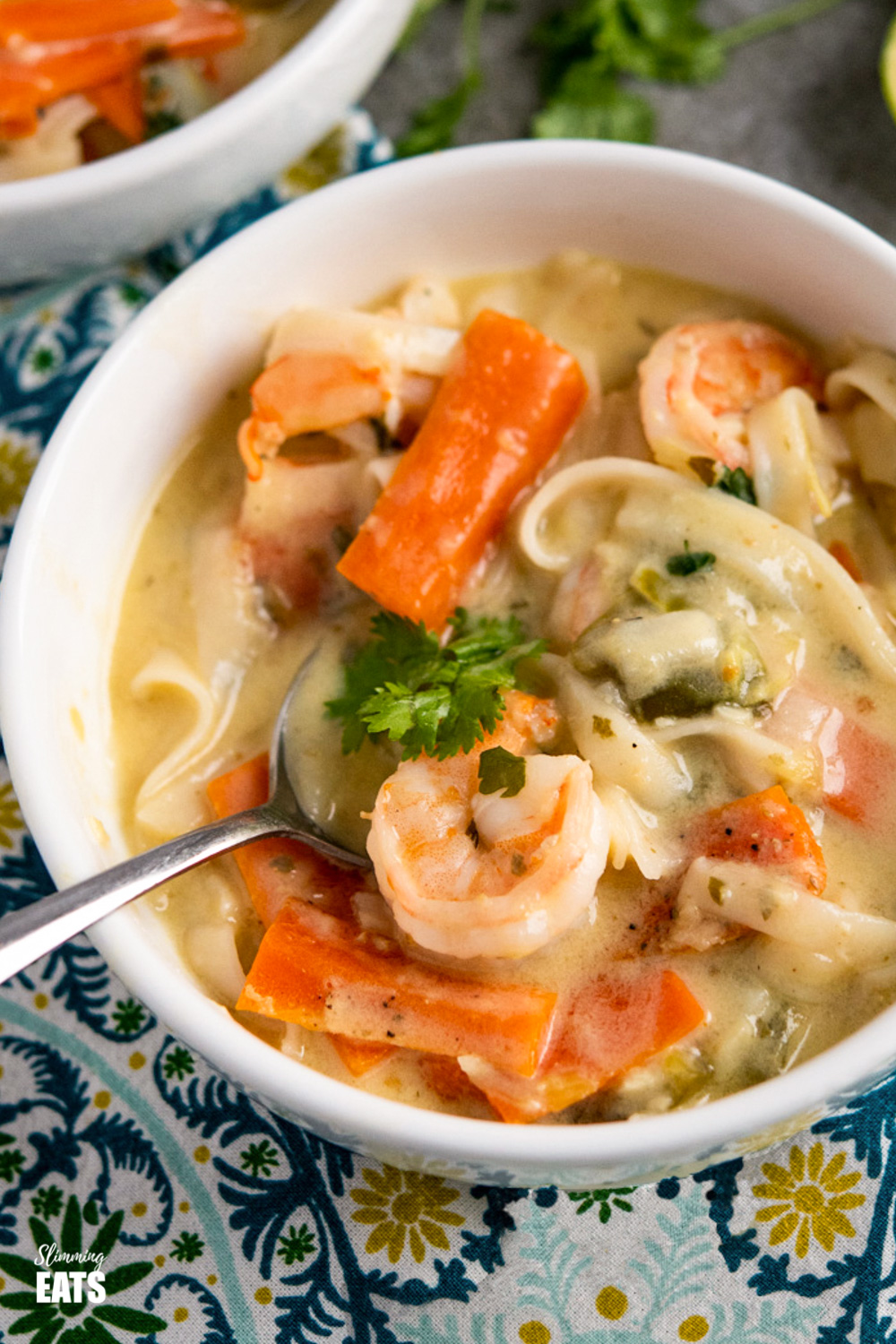 close up of Thai Coconut Shrimp Noodle Soup in white bowl with spoon