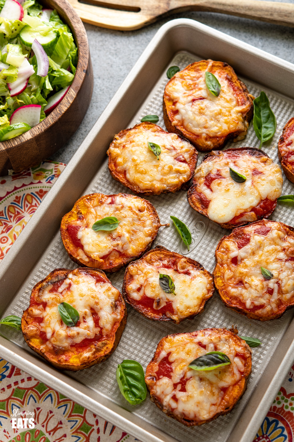 air fryer pizza sweet potato slices on a baking tray with scattered fresh basil and bowl of salad to the left