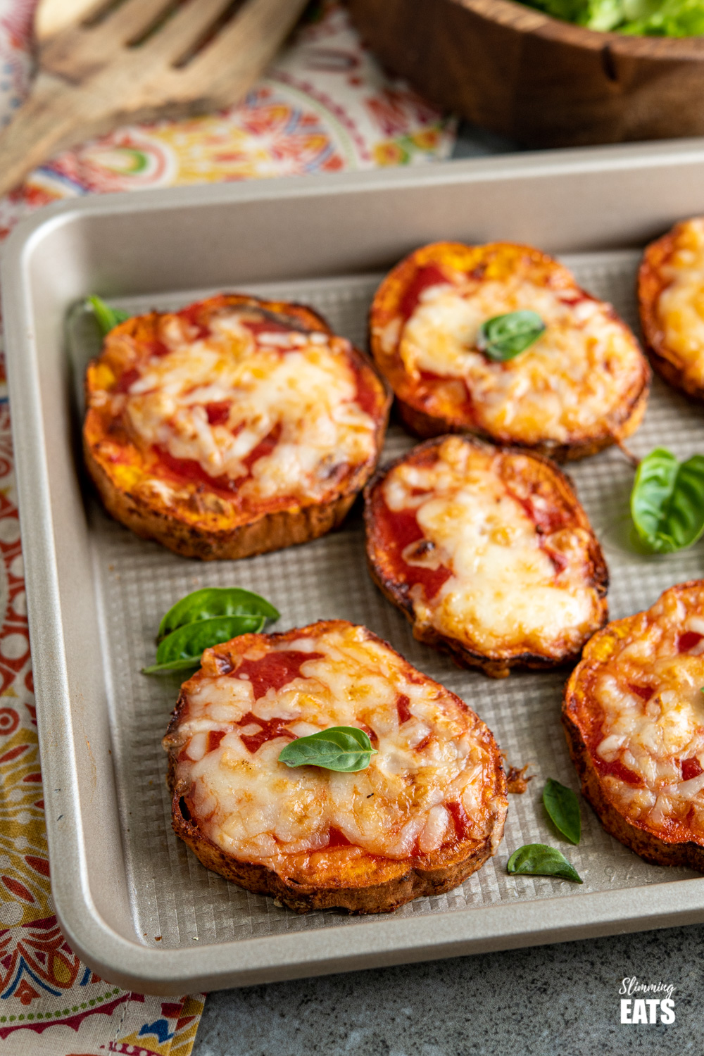 pizza sweet potato slices on baking tray on patterned napkin with bowl of salad and spatula in background