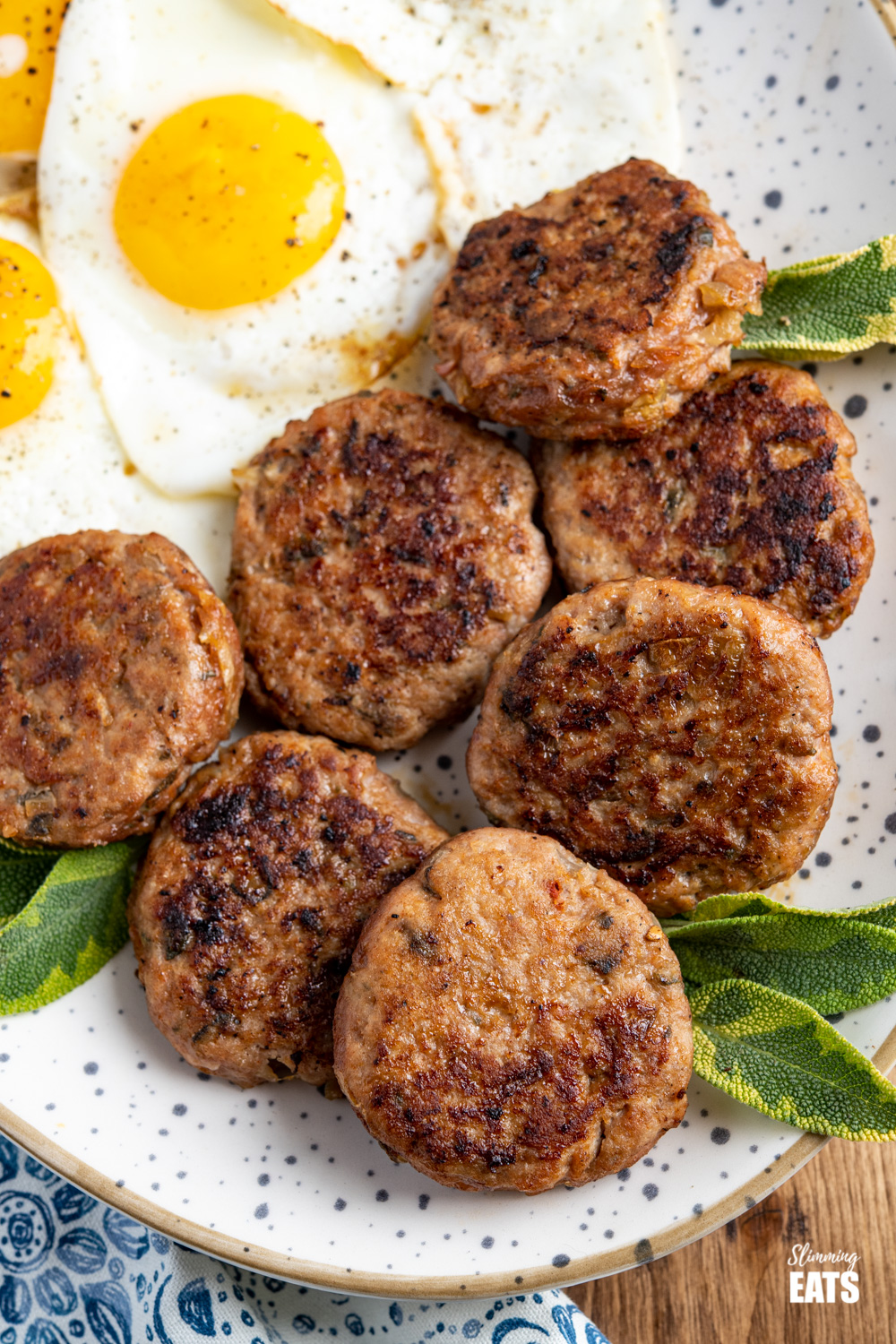 close up of oval speckled plate filled with homemade turkey breakfast sausage patties and fried eggs
