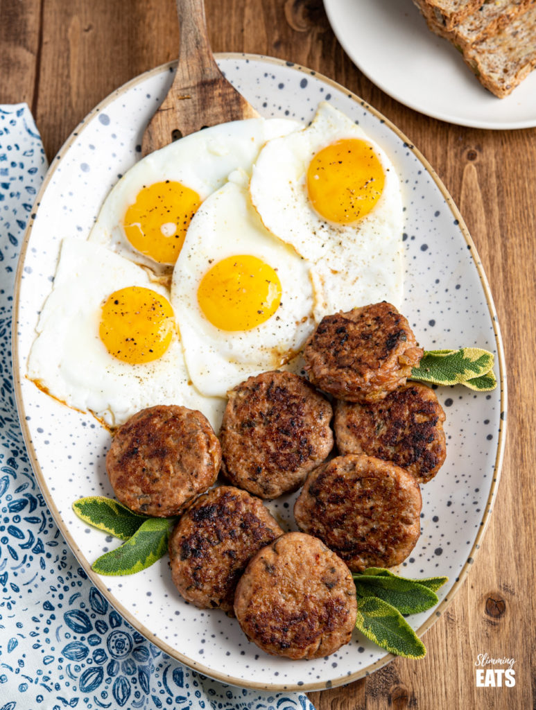 oval speckled plate filled with homemade turkey breakfast sausage patties and fried eggs, plate of wholemeal bread in the background