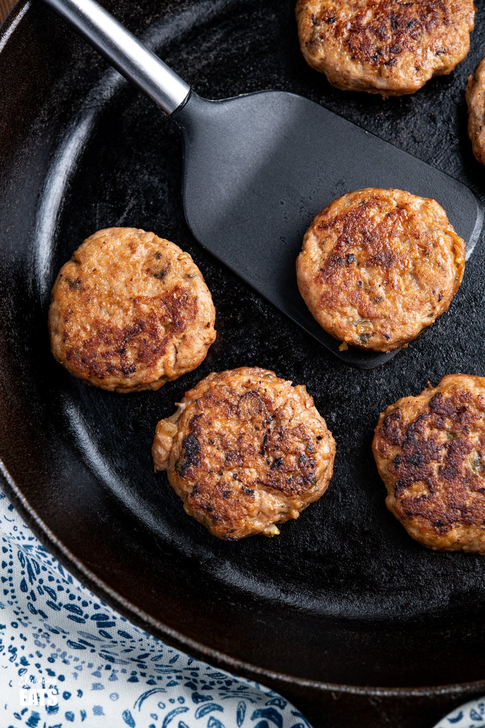 close up of cooked Turkey Breakfast Sausage Patties in a lodge cast iron skillet on spatula