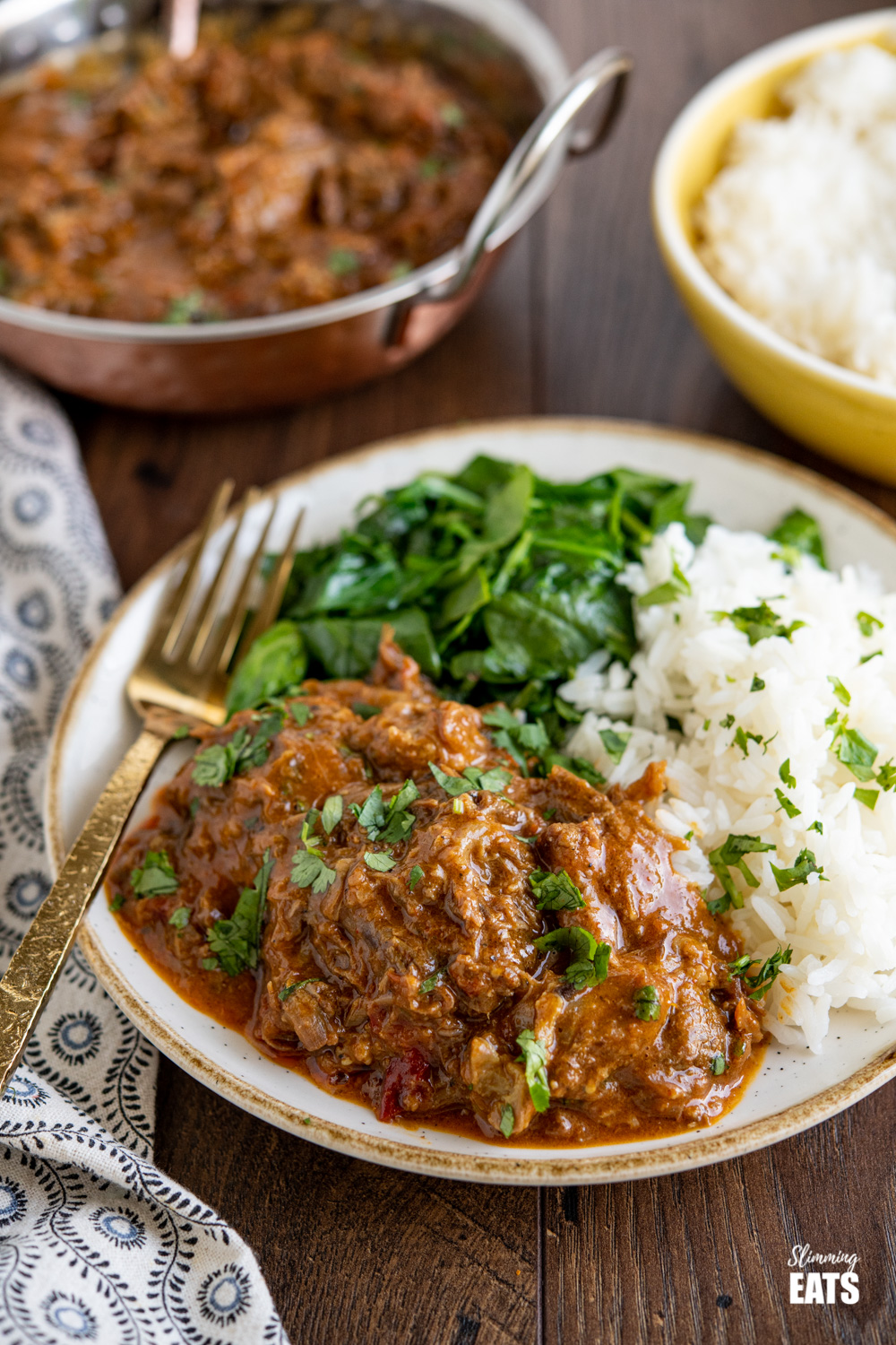 lamb bhuna on beige and white plate with rice, spinach and sprinkled with coriander