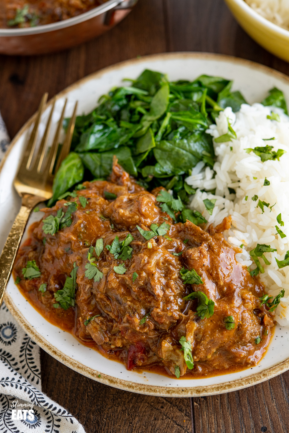 close up of lamb bhuna on beige and white plate with rice, spinach and sprinkled with coriander