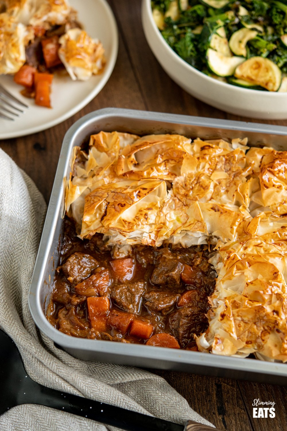 Steak and Vegetable Pie in baking tin with bowl of green vegetables in background