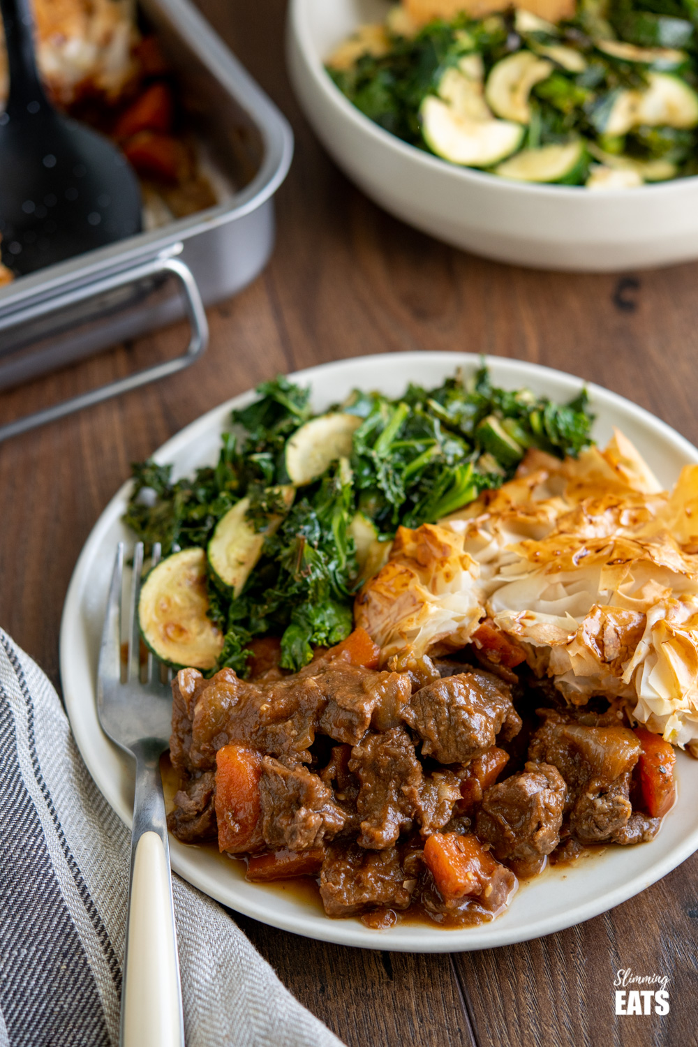 Steak and Vegetable Pie on plate with zucchini and kale