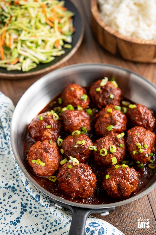 boulettes de poulet au miel et à l'ail dans une poêle en acier inoxydable avec légumes sautés et riz en arrière-plan