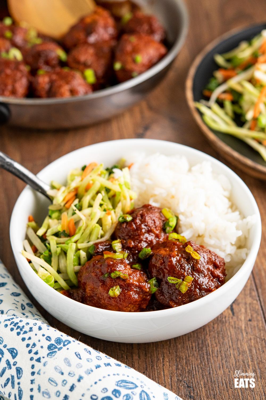 boulettes de poulet au miel et à l'ail dans un bol blanc avec légumes et riz
