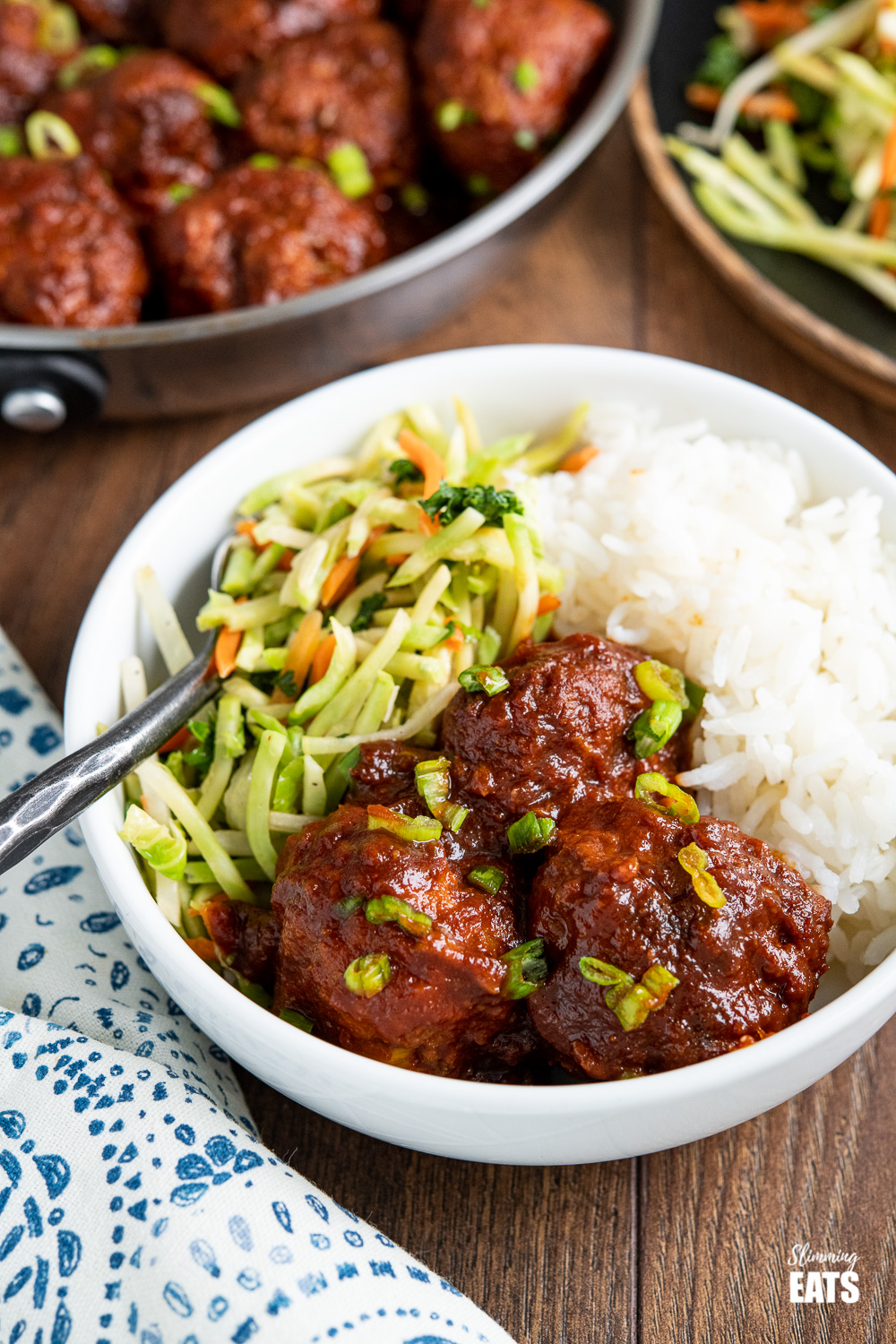 close up of honey and garlic meatballs in a white bowl with veggies and rice
