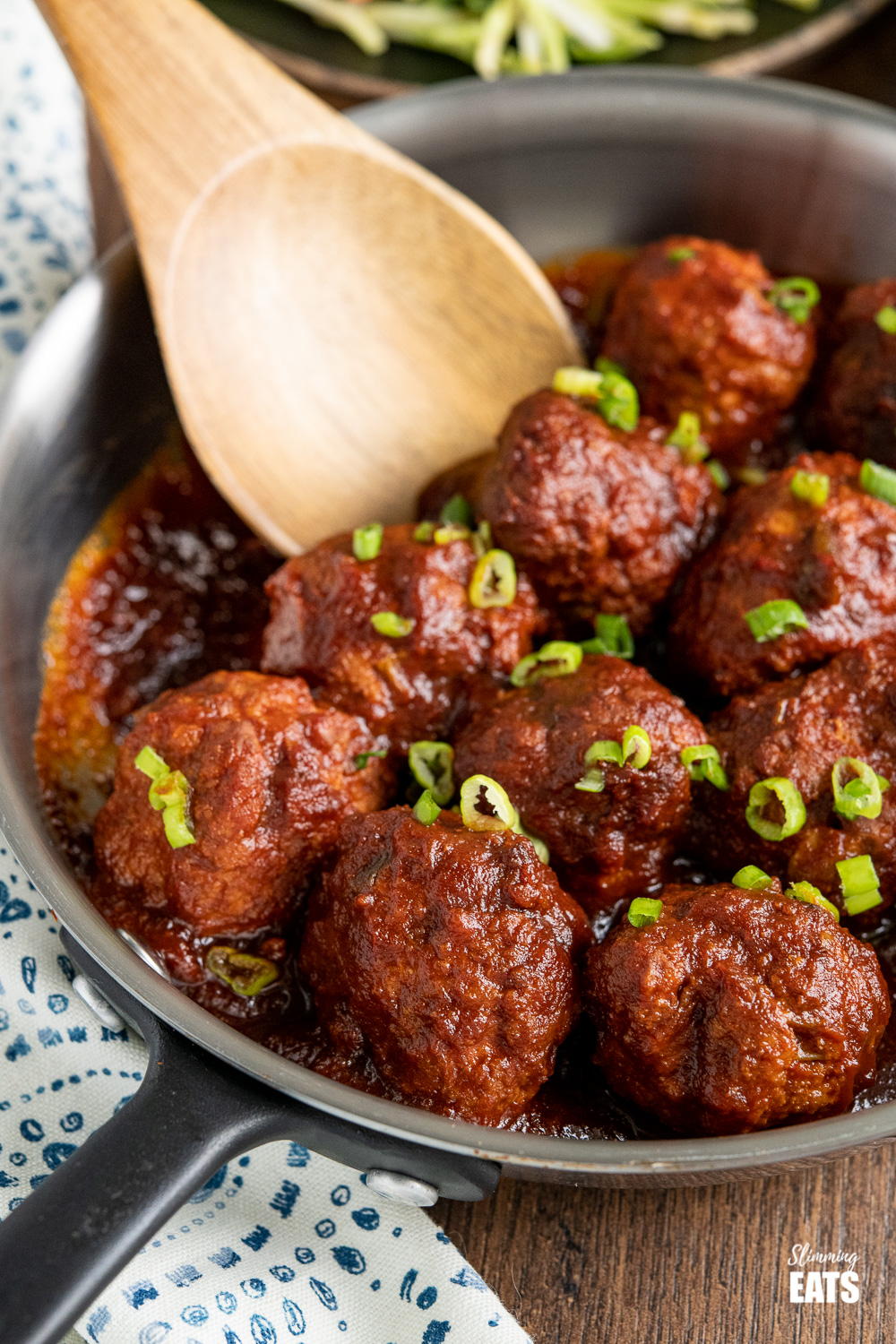 close up of honey and garlic chicken meatballs in a stainless steel frying pan with wooden spoon