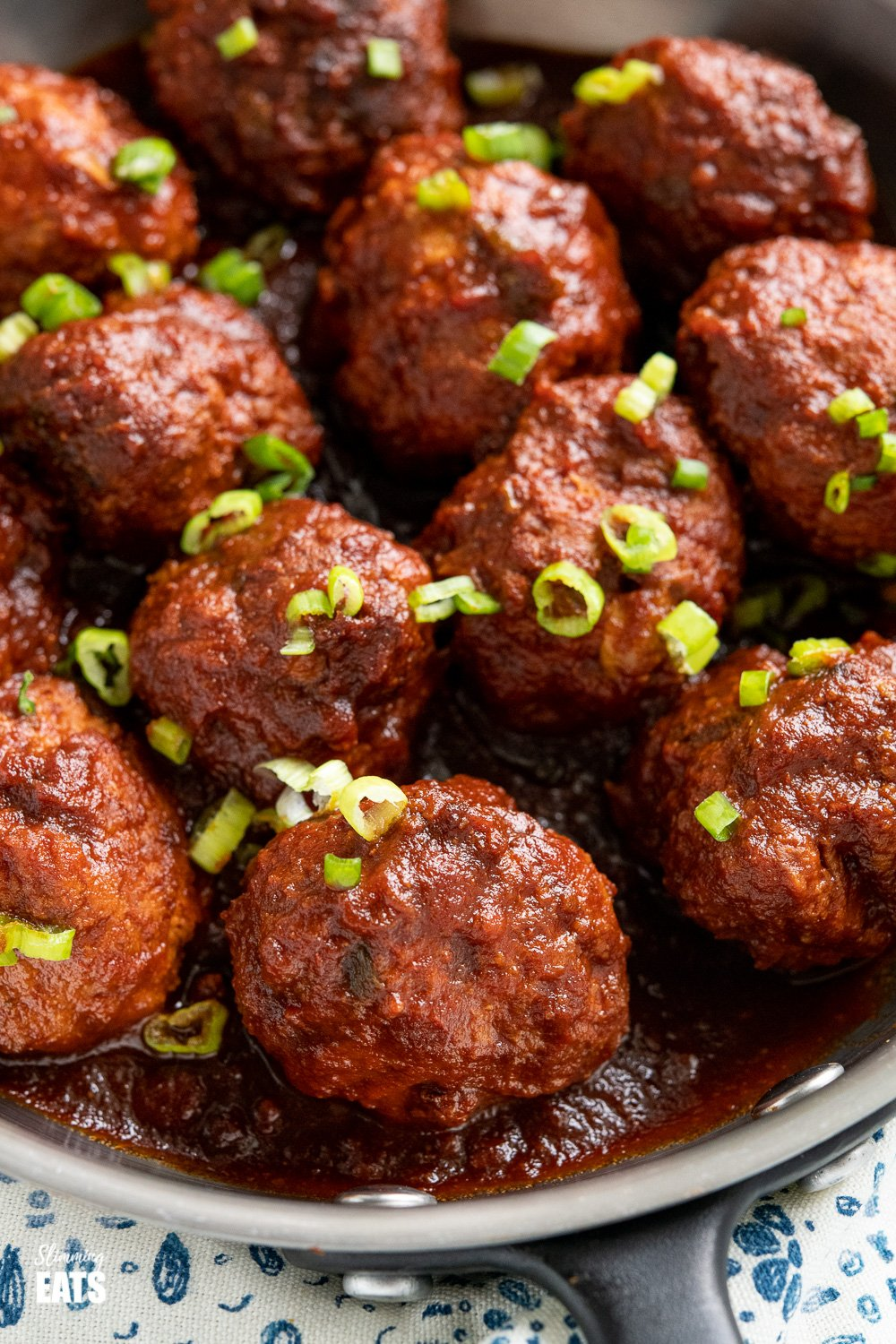 close up of honey and garlic meatballs with sauce in pan sprinkled with chopped spring onions