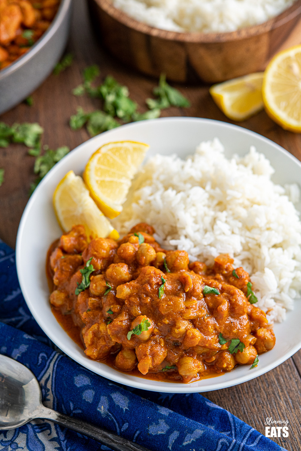 vegan tikka masala in white bowl with rice and lemon wedges