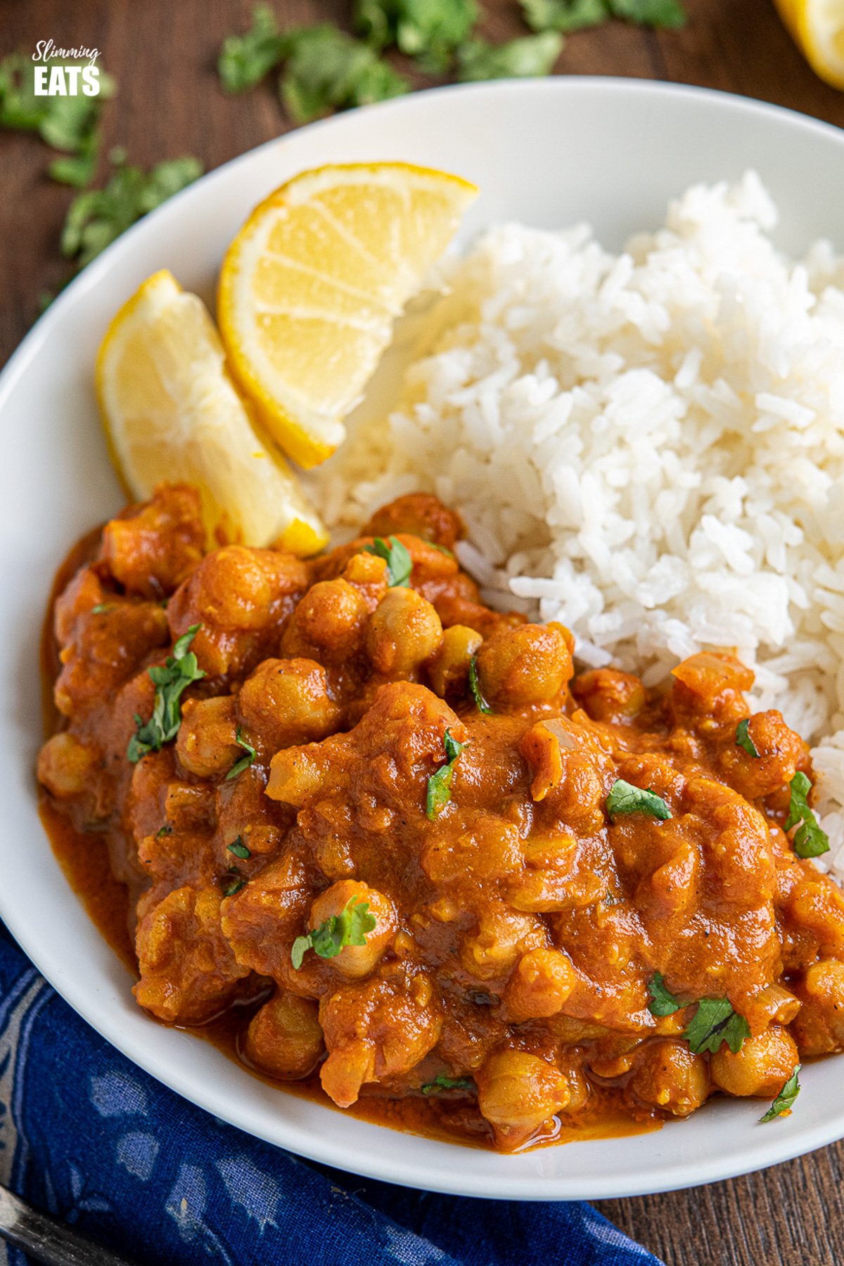 close up of vegan tikka masala in white bowl with rice and lemon wedges