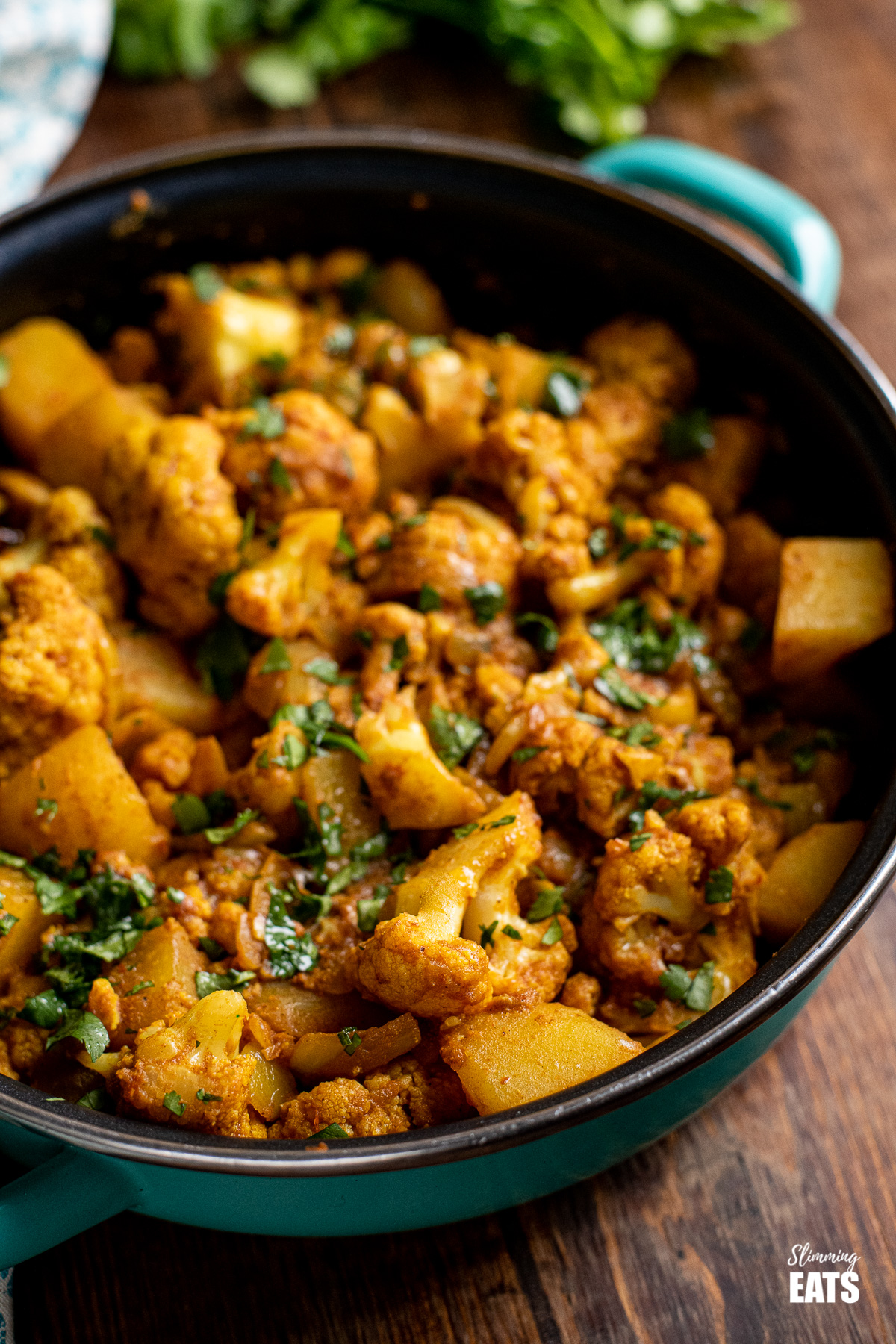 aloo gobi in frying pan with cilantro in background