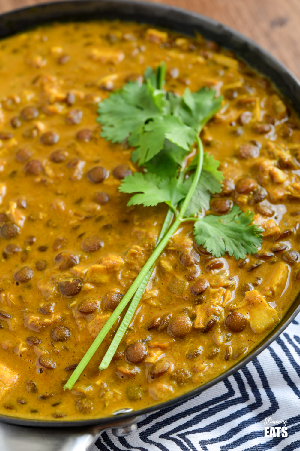 close up of coconut chicken and lentil curry in a frying pan topped with some fresh coriander