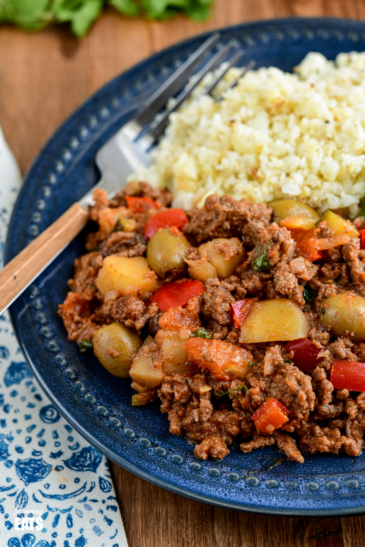 close up of Cuban Beef Picadillo with cauliflower rice on dark blue plate.