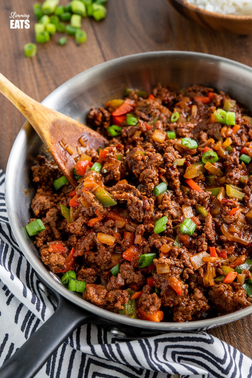 easy asian ground beef in frying pan with wooden spoon, scattered spring onions and black and white napkin