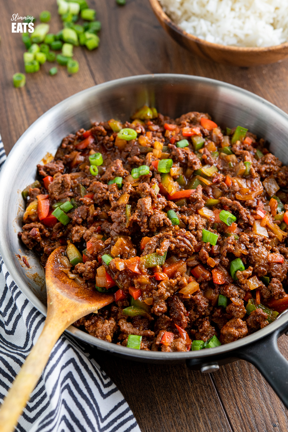 easy asian ground beef in frying pan with wooden bowl of jasmine rice in background