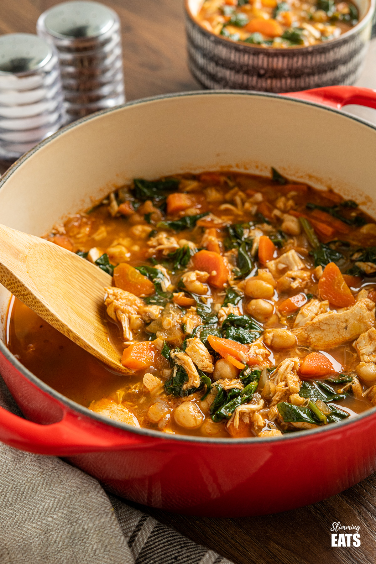 Chicken Chickpea and Spinach Soup in red cast iron port with wooden spoon on with cup of soup in backgrounders
