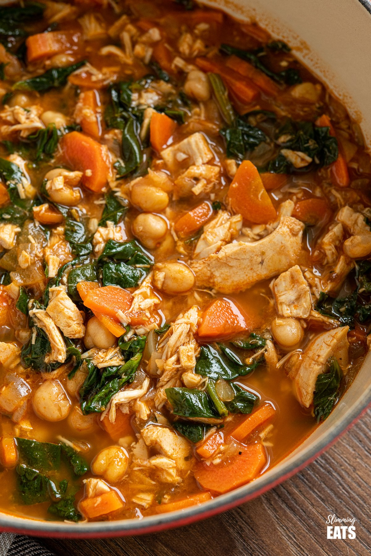 close up of chicken chickpea spinach soup in cast iron pot