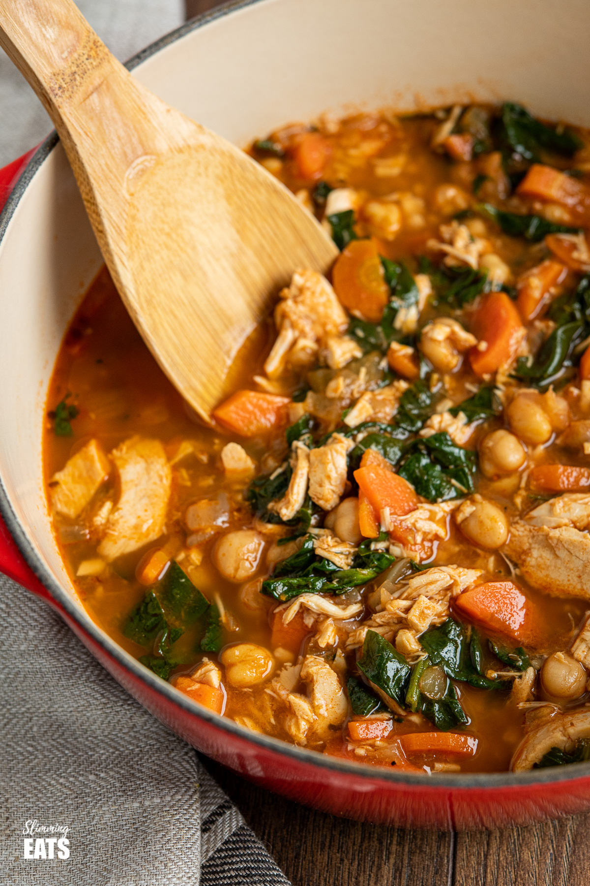 close up of chicken chickpea spinach soup in red cast iron pot with wooden spoon