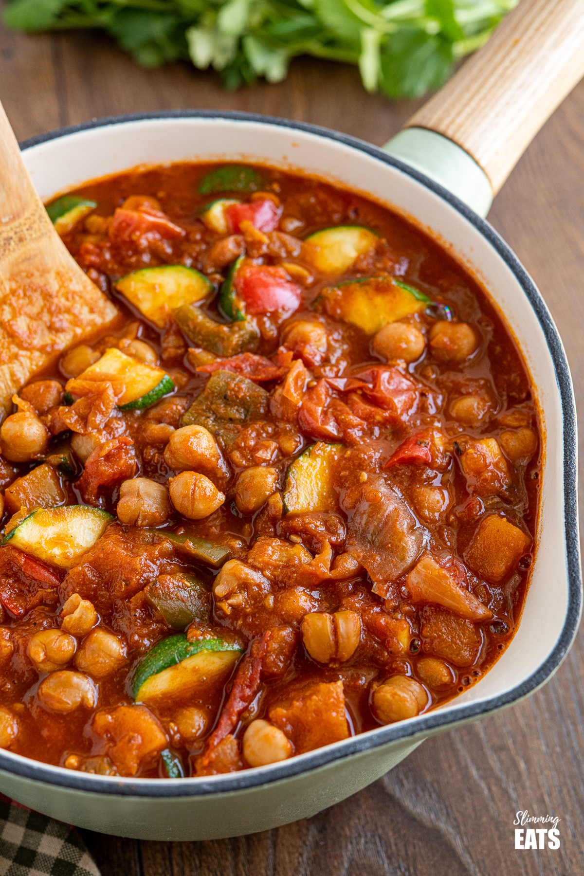 close up of chickpea vegetable chilli in a wooden handled cast iron pot