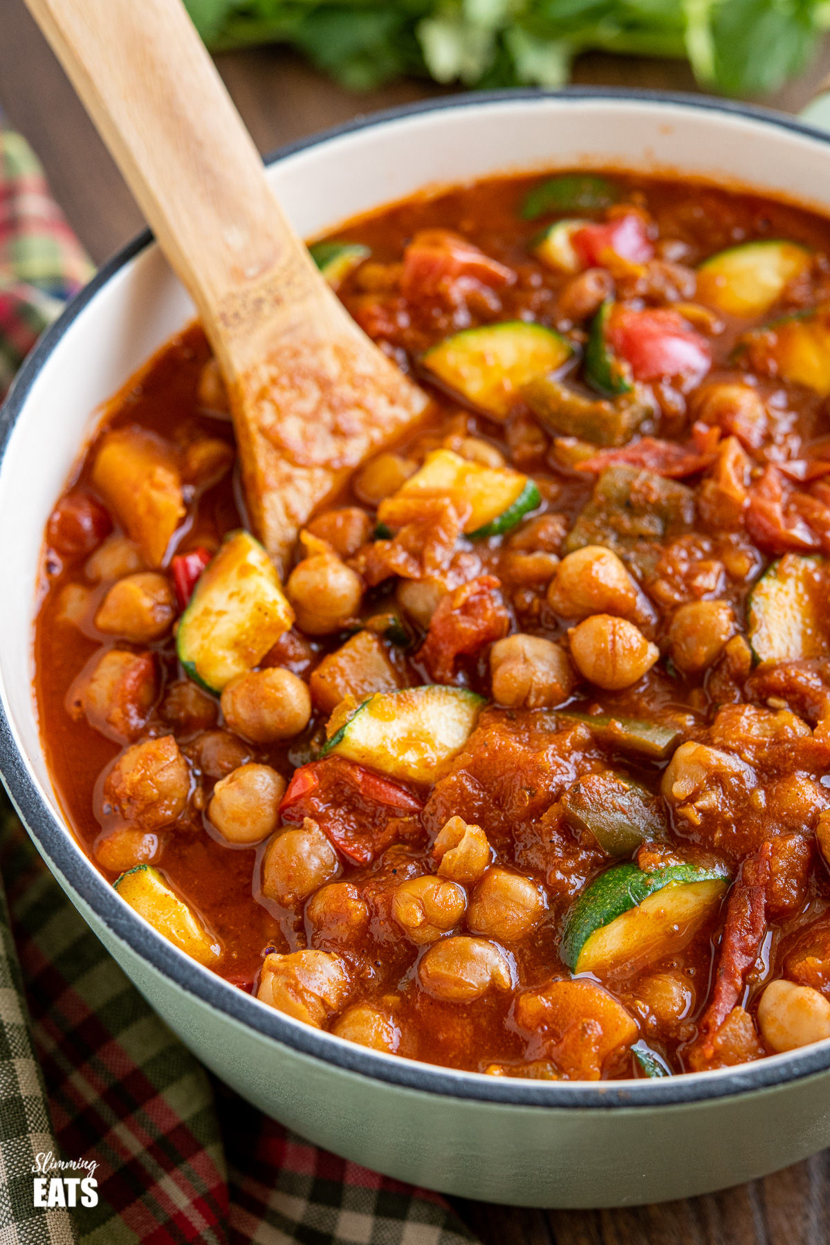 close up of chickpea vegetable chilli in cast iron saucepan with wooden spoon